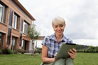 Germany, Bavaria, Nuremberg, Mature woman using digital tablet in garden