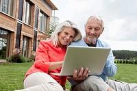 Germany, Bavaria, Nuremberg, Senior couple using laptop in garden