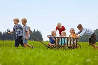 Germany, Bavaria, Group of children playing with hand cart