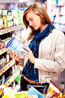Woman shopping in baby food section in supermarket.
