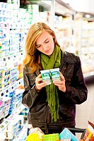 Woman shopping for dairy products in supermarket.