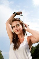 Germany, Berlin, Young woman listening music, close up