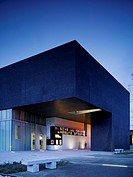 Solstice Arts Centre, Navan, Ireland. Architect: Grafton Architects, 2006. View of entrance showing glazed lower level and granite cladding on upper l...