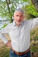 Smiling senior man standing on lakeside