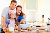 Family with baking ingredients behind the kitchen counter