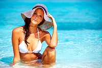 Portrait of attractive woman wearing sun hat relaxing in water