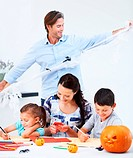 A young family making Halloween decorations together