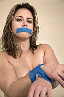 Woman´s wrists and mouth taped