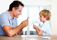 A father and son playfully face off during a game of cards