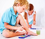 A brother and sister enjoying some time together painting pictures with watercolours