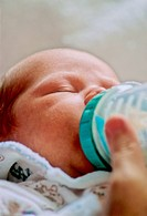 A close up of a baby drinking milk from a nursing bottle.