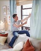 Interior designer Nate Berkus cutting blue living room curtains