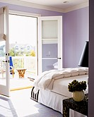 French doors in a lavender guest bedroom open onto a terrace
