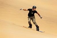Sand boarding in the dunes of the Namib Desert near the coastal town of Swakopmund has become very popular  Swakopmund, Namibia