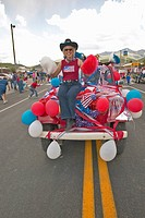 Woman sitting on the hood of a jeep decorated for the Fourth of July, in Lima Montana