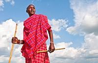 Kenya Masai Mara Masai warrior in red traditional wrap and stick in Masai Mara National Park in reserve 9