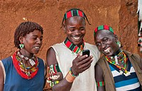 Dimeka Ethiopia Africa village Lower Omo Valley portrait of young Hamar guys and girl texting with cell phone communicating 18