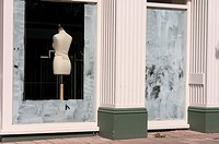 Fashion mannequin seen through whitewashed windows of an out of business closed shop.