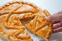 Man´s hand taking a piece of Spanish pie. Close view.