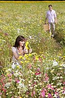 Smiling couple with picnic basket in meadow with wildflowers