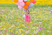 Portrait of smiling girl holding bunch of balloons among wildflowers in sunny meadow