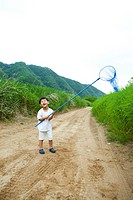 Boy carrying butterfly net in field