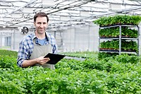 Germany, Bavaria, Munich, Mature man in greenhouse between parlsey plants with clip board