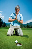 Man kneeling near a golf hole and praying