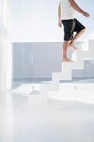 Spain, Mid adult man walking up stairway