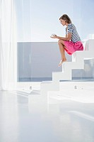 Spain, Mid adult woman sitting on stairway with cup