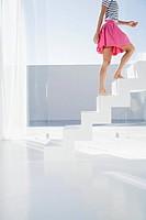 Spain, Mid adult woman walking up stairway