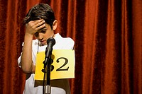 Boy contestant standing at microphone thinking