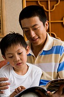 Father and son reading magazine