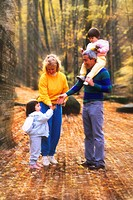 Grandparents take their granddaughters on a nature walk to enjoy the beautiful fall colors