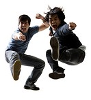Portrait of two young men jumping and kicking
