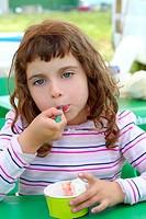 brunette little girl eating ice cream