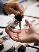 Close_up of a person giving a car key to another person