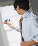Profile of a businessman holding up color swatches
