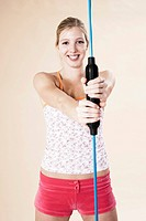 Young woman doing sport exercises with a vibrating rod