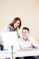 Woman helping a boy on a computer