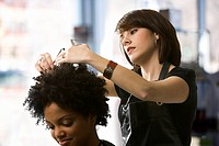 Female hairdresser trimming a young womans hair