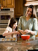 Girl in kitchen with woman baking cookies