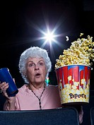 Woman watching film at movie theatre frightened