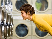 Woman watching clothes in dryer at Laundromat