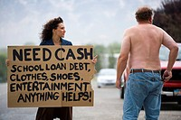 Young woman holding a help_needed sign and looking at a man