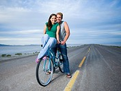 Portrait of a young woman and a mid adult man sitting on a bicycle