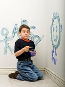 Portrait of a boy painting on a wall