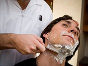 Close_up of a young man getting a shave at a barber
