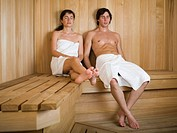 Young couple sitting on a wooden bench in a sauna