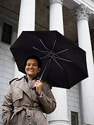 Low angle view of a woman holding an umbrella and smiling